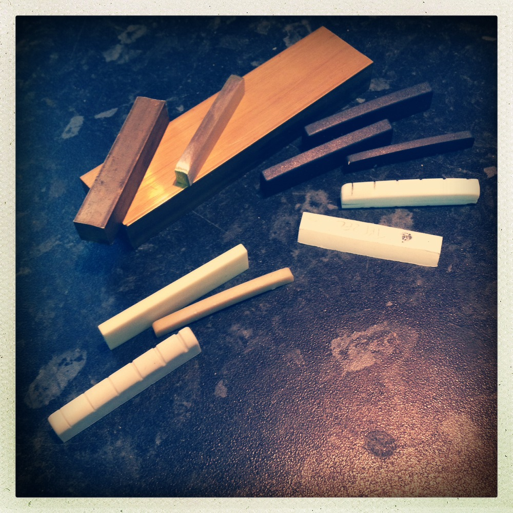 Clockwise from bottom: Tusq and Micarta, Brass nuts and blanks, Graphite nuts, Corian, Tefzel
