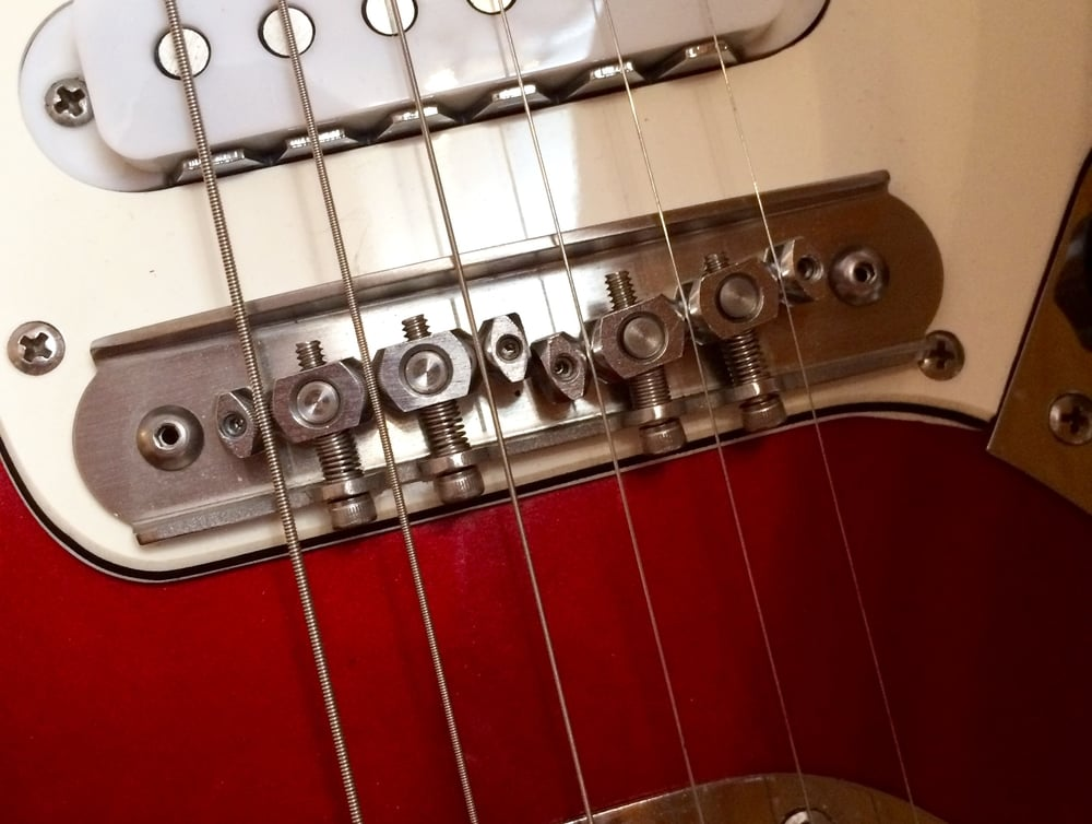 Turning adjustment screws alters overall angle (and intonation) for three strings at a time