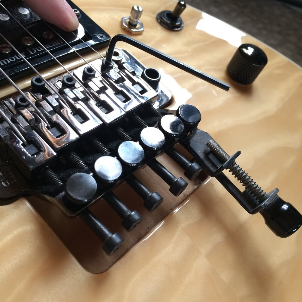 Adjusting intonation on a Floyd Rose (using The Key in this instance). Allen wrench loosening saddle screw.