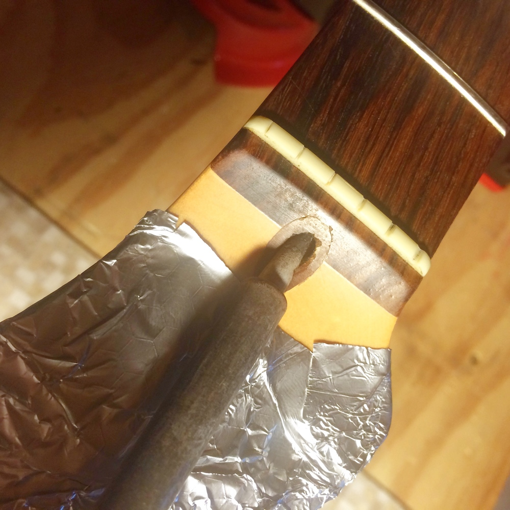Use a soldering iron to heat the walnut plug concealing the Fender truss rod nut. You don't need to actually touch the wood.