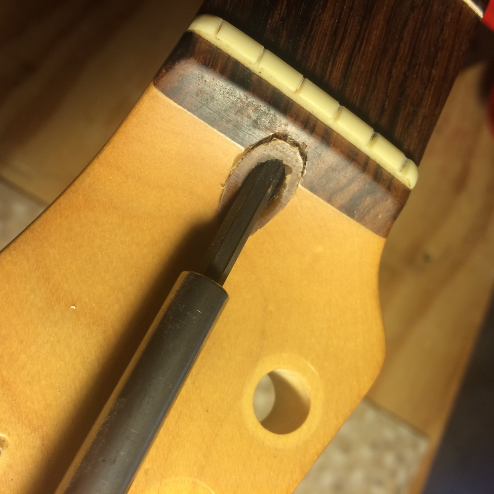 Backing out the truss rod nut will push the plug out (assuming the glue's sufficiently softened of course).