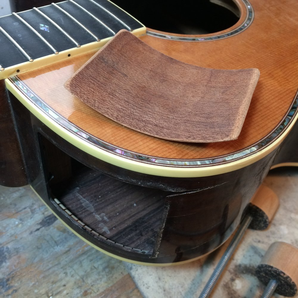 The patch piece before it's glued in to the side of this acoustic