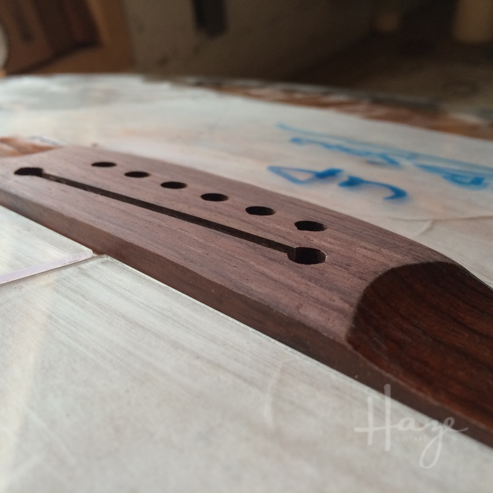 Lowering the top of the acoustic guitar bridge.