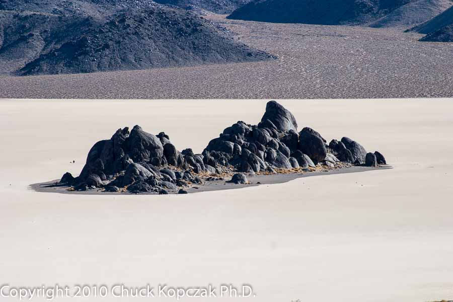 The Grandstand, an extrusion of dark quartz-monzonite, protrudes through the dry lake bed in Death Valley known as the Racetrack.