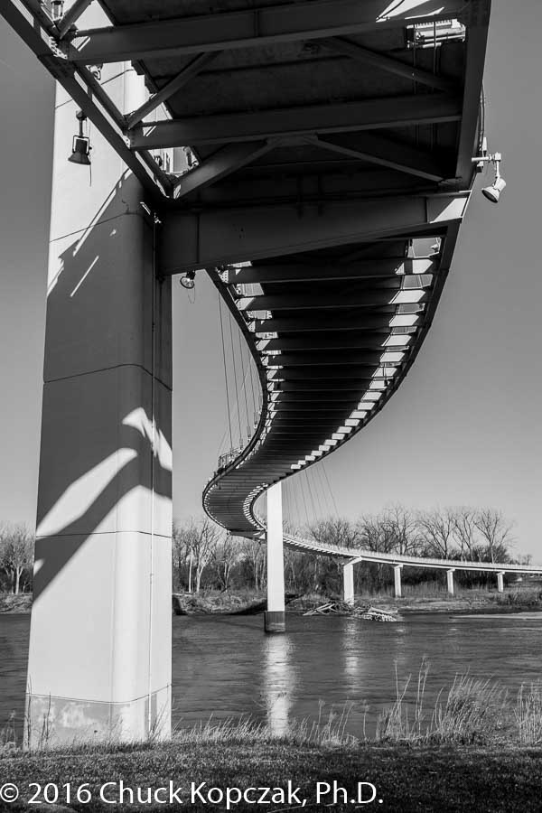 Curving above the Missouri River, the Bob Kerrey Pedestrian Bridge sinuously connects the cities of Omaha, Nebraska, and Council Bluffs, Iowa.