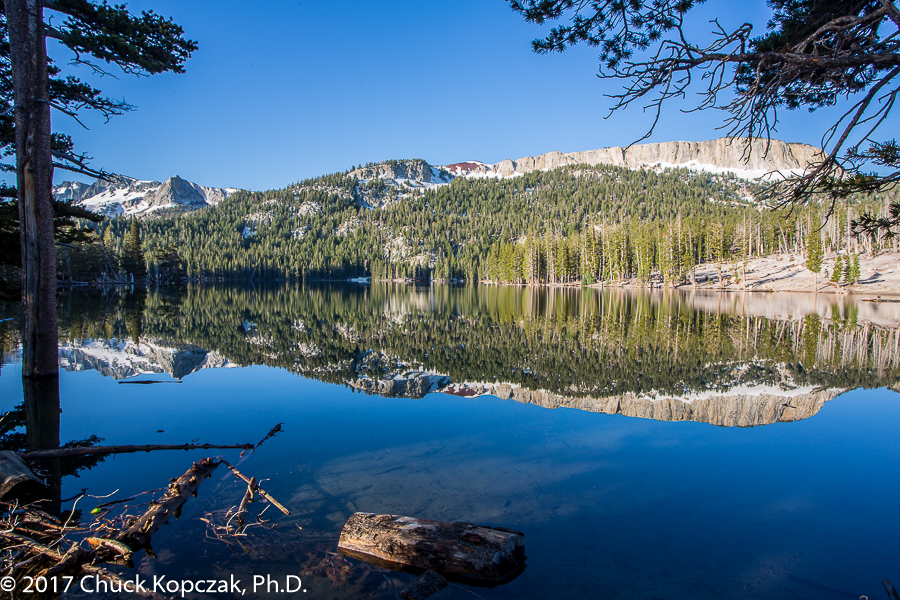 The norther end of the Mammoth Crest is reflected in the still waters of Horseshoe Lake in the Mammoth Lakes Basin, California.