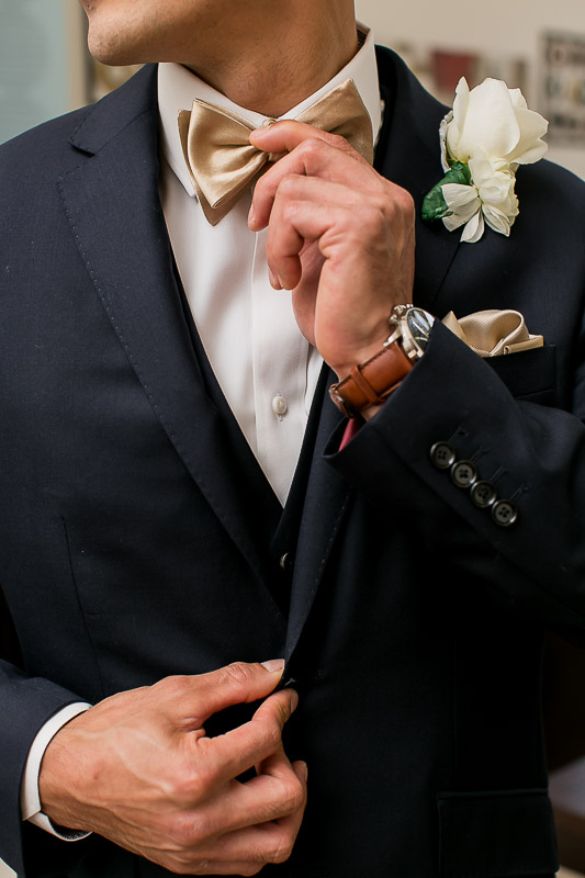 Groom wedding details with gold bowtie, blue suit, watch and pocket square