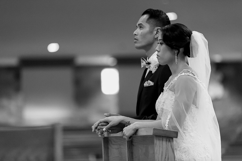 Bride and Groom kneeling at altar at St Paul the Apostle Catholic Church in Chino Hills, CA