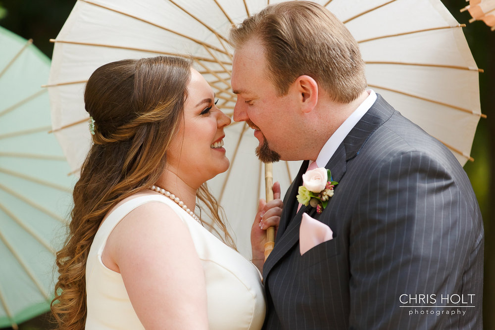 Happy Bride and Groom kiss in front of paper parasols