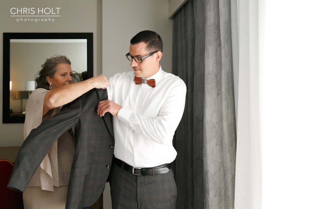 mother of the groom putting jacket on her son