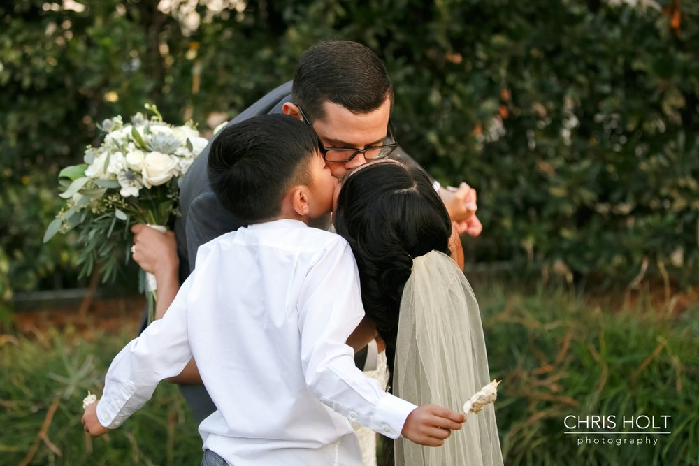 Bride Groom and Ringbearer hugging and kissing as a new family