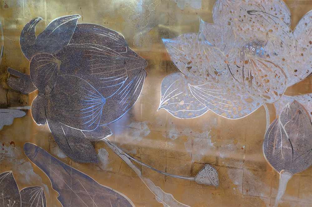 Inspired by the elephants, frogs and lotus flowers featuring in the hotel lobby's fountain, Emma Peascod created three verre églomisé panels with golds, grey-blues, pink, turquoise and yellow-greens.