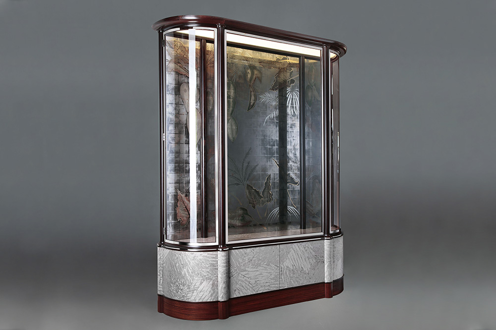 Bespoke display cabinet for a super yacht produced in collaboration with furniture maker Richard Williams featuring interior glass panels in pewter-coloured gold.