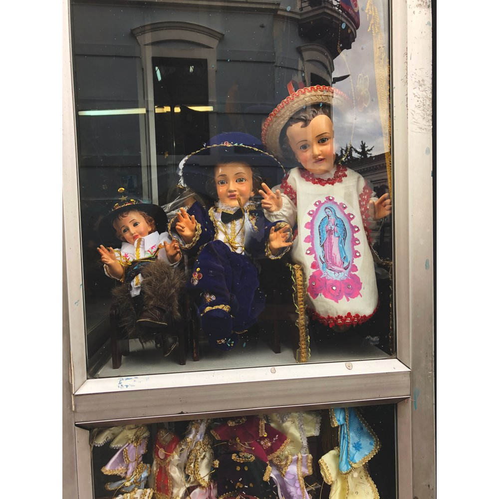 Shop window in Centro Historico, Quito.  This street was devoted to selling religious dolls and the clothes to dress them.  Each street had a different item to sell.  For instance, one street was filled with yarn shops, the next with religious candle shops, and so on.