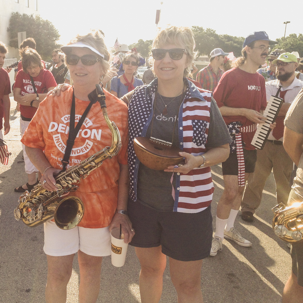 Several gathered, instruments in hand, to hang out before marching and playing wonderful cacophonous music together.