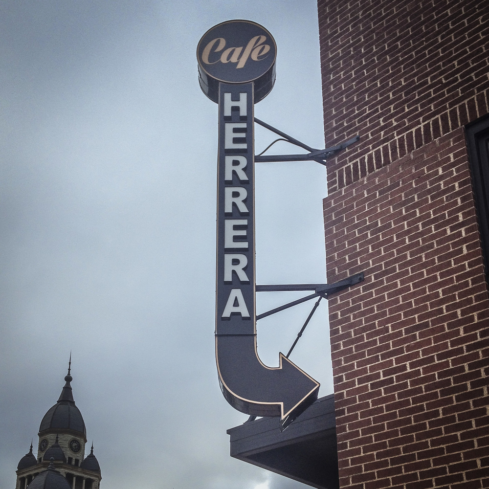 Herrera's got their new sign up at the corner of Oak and Locust. We like it a lot more than the sign it's next to.