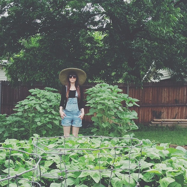 @jadewintersee  posed in her yard full of sunflower stalks.