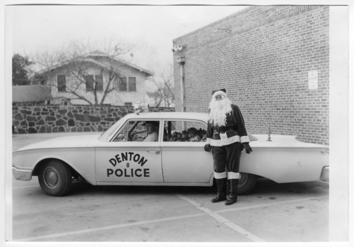 Sheriff Andy Anderson assists Santa in helping spread some Christmas cheer to Denton residents, circa 1960s. Photo from texashistory.unt.edu.