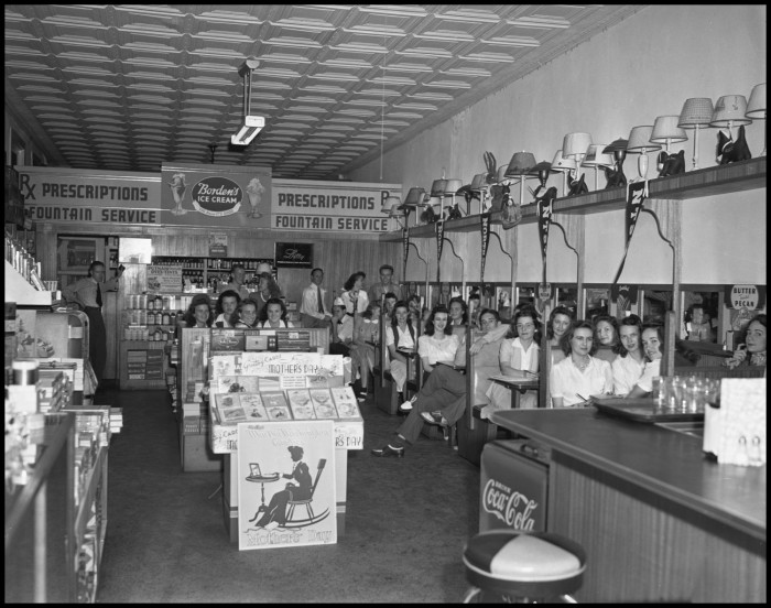 1942 Photograph of customers at the Hamilton Drug Store in Denton, with a display of Mother's Day cards sitting in the center of the room. Photo from TexasHistory.unt.edu.