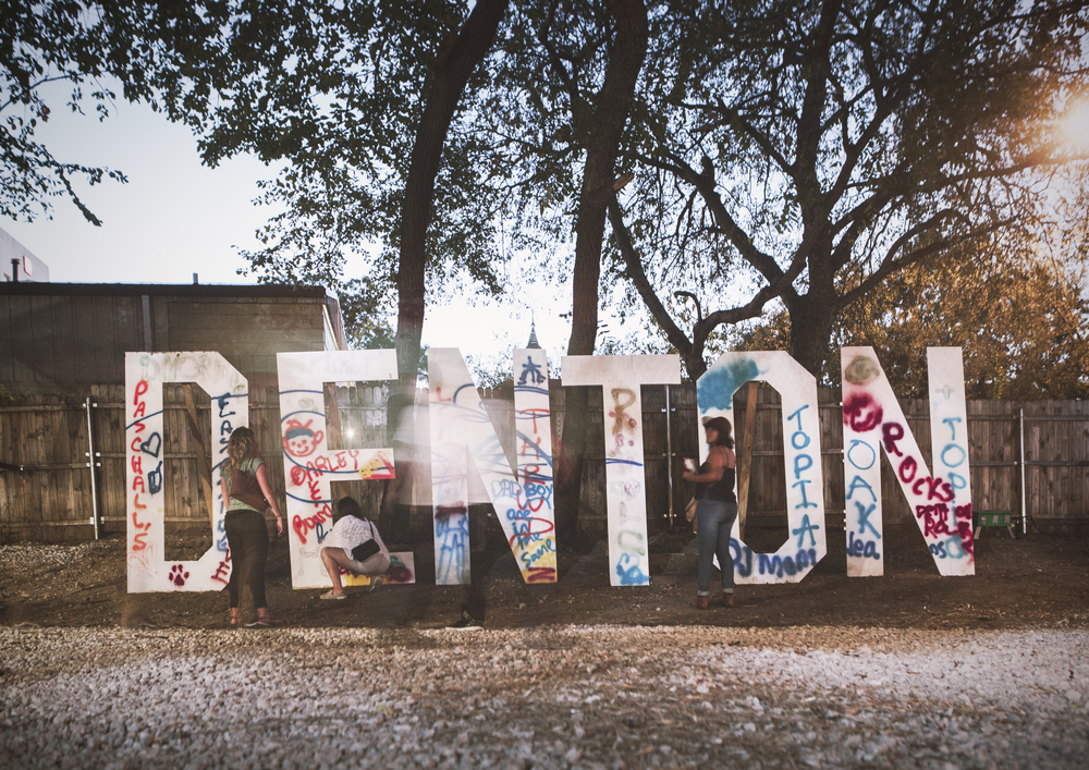 """There were plenty of signs, murals, and pieces of art around town (and many with the town's name on it). Here's a pic from Oaktopia with folks walking by and tagging """"Denton."""""""