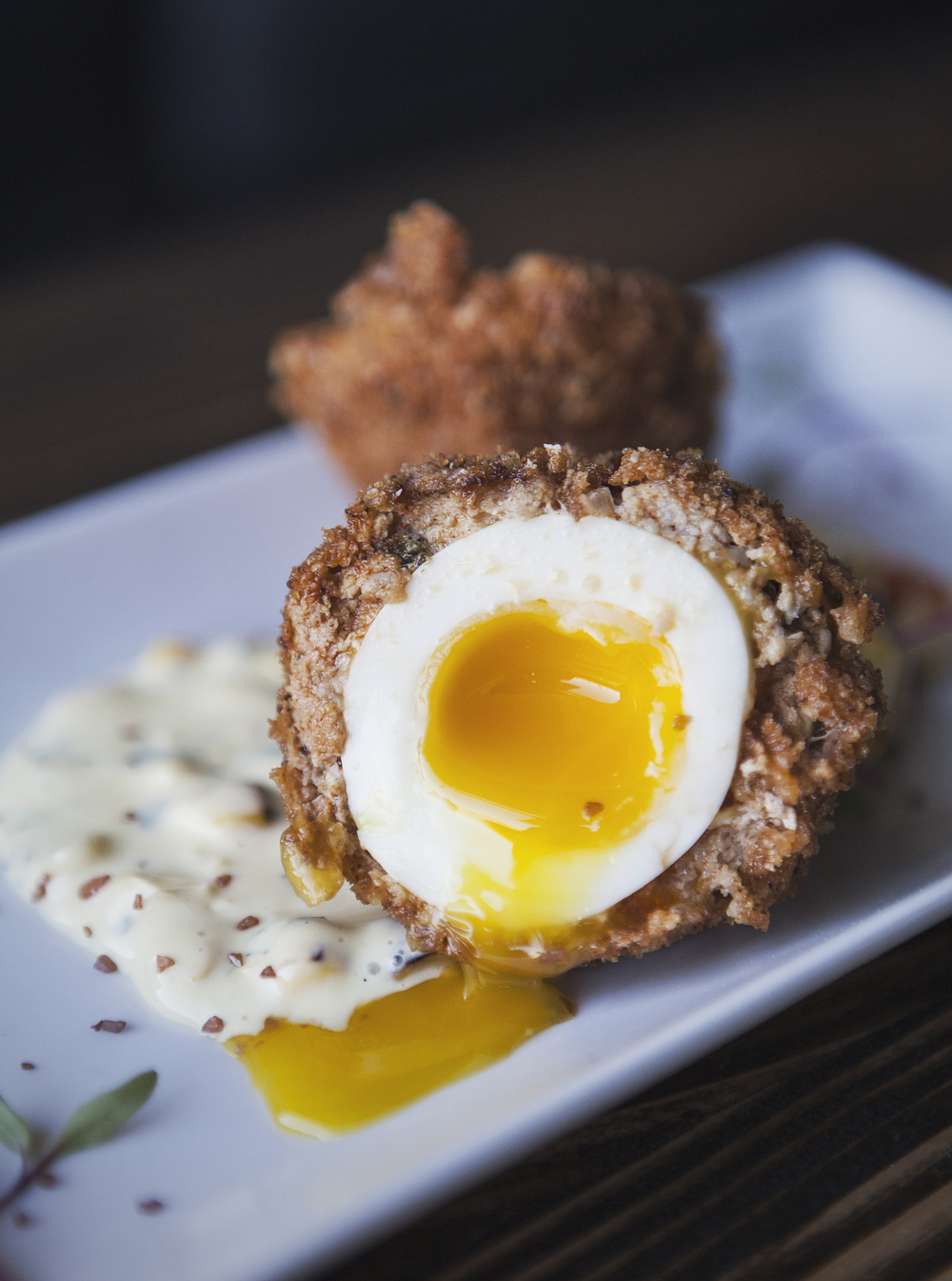 The scotch egg complete with runny yolk.