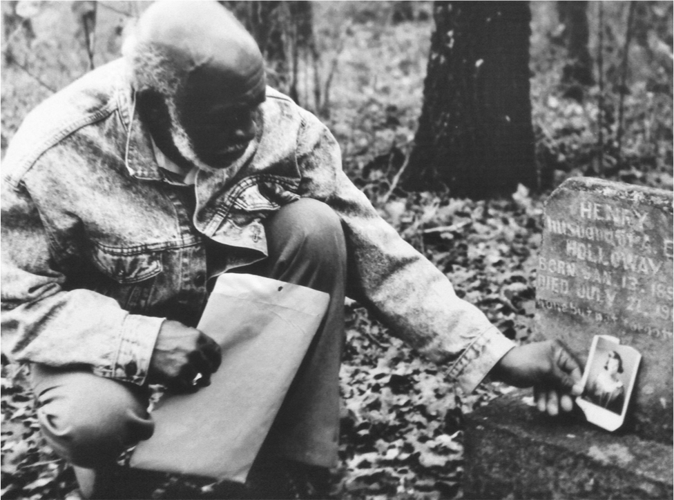 Eli Sledge visits the grave of his uncle Henry Holloway in the Saint John's Cemetery near Pilot Point, 1998. Photo courtesy of Denton County Historic Commission.