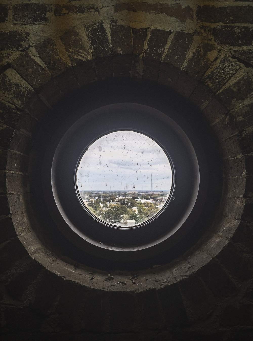 Looking at downtown Denton from a small circular window deep within the bowels of the courthouse. Photo by Will Milne.