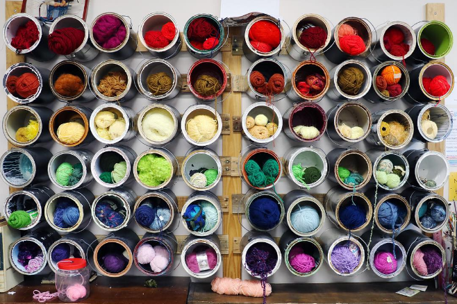 SCRAP's paint bucket wall full of yarn from @justinpeacedfw.