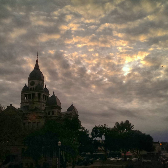 @lezapics with a photo of the courthouse against a cloudy fall sky.