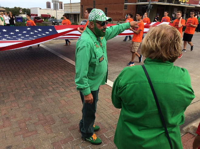Frenchy wearing green (even his beard which we hope was made green through the use of dye), but standing in front of people wearing orange. Photo by @tomleininger.photo.