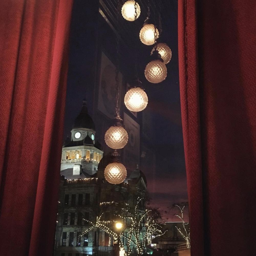 @jodidallas peeking through the red curtain at Paschall Bar.