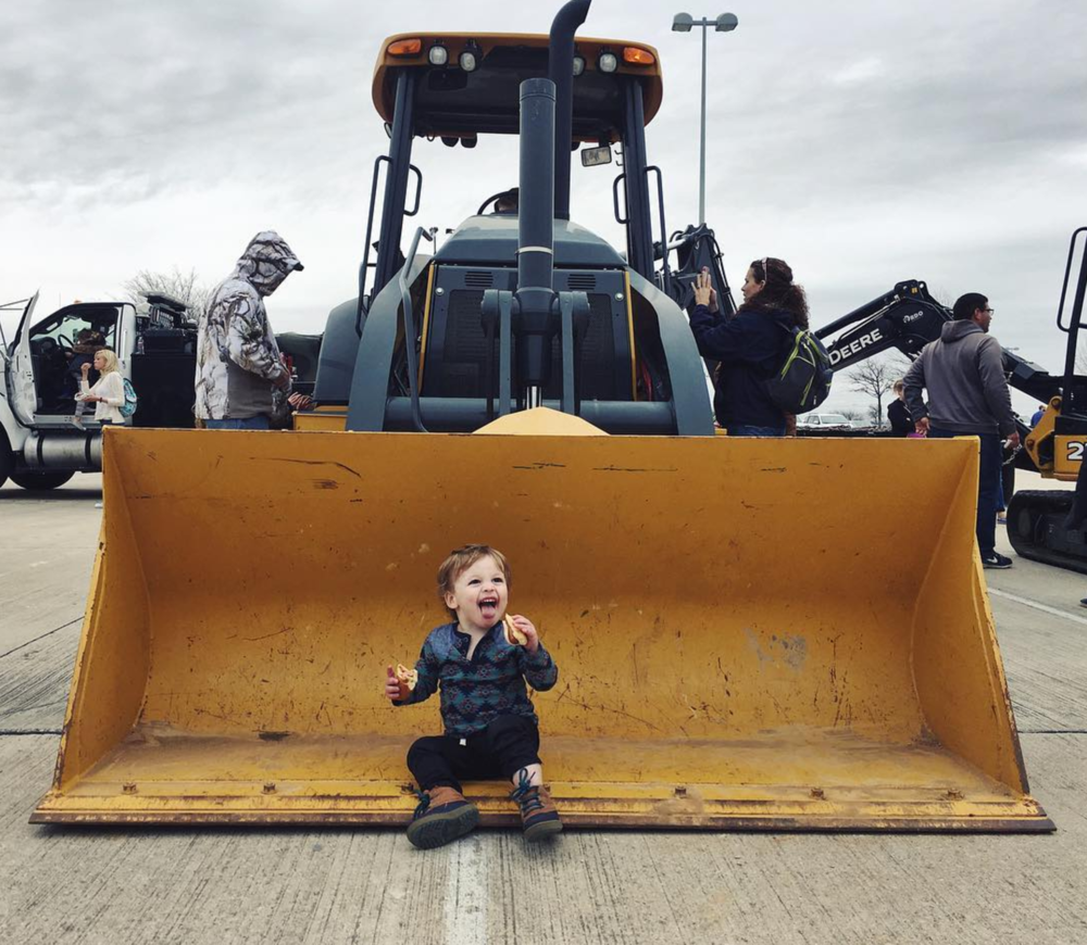 Double-fisting hot dogs and checking out some large machinery at this year's Touch-A-Truck event at C.H. Collins on Saturday. Photo by @erin.k.jones.