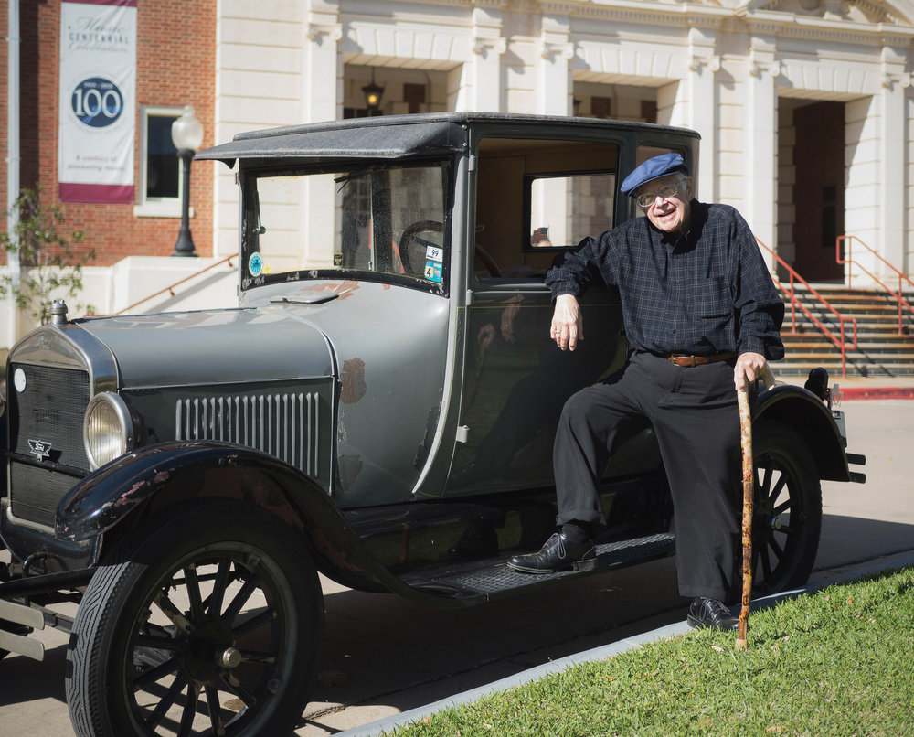An older gentleman with his Model T Ford that he has owned for over 70 years.