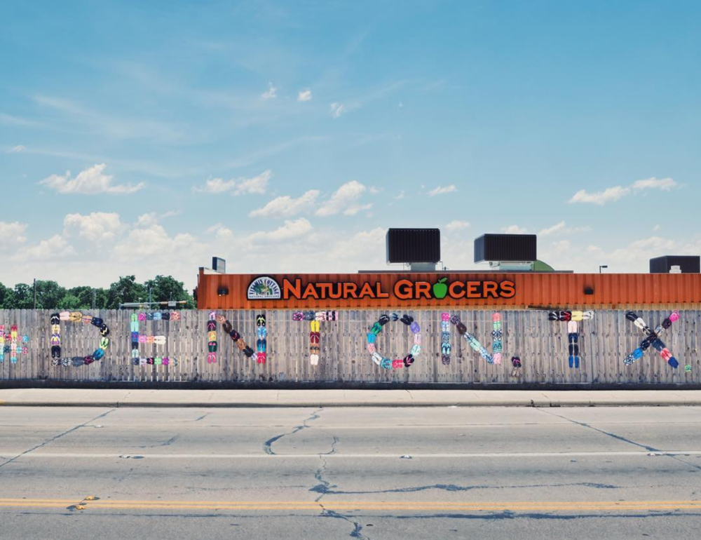 The recently re-decorated Adopt-A-Spot fence on Sherman behind Natural Grocers overseen by Judy Smith of Rose Costumes fame. Photo by @wedentondoit.