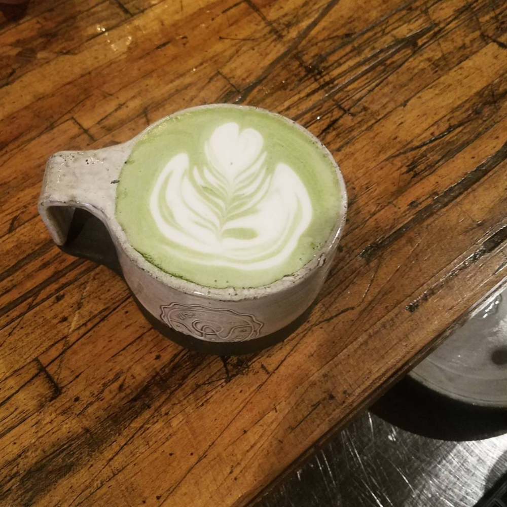 A vibrant matcha latte from West Oak Coffee Bar. Photo by @thepaulbunyan.