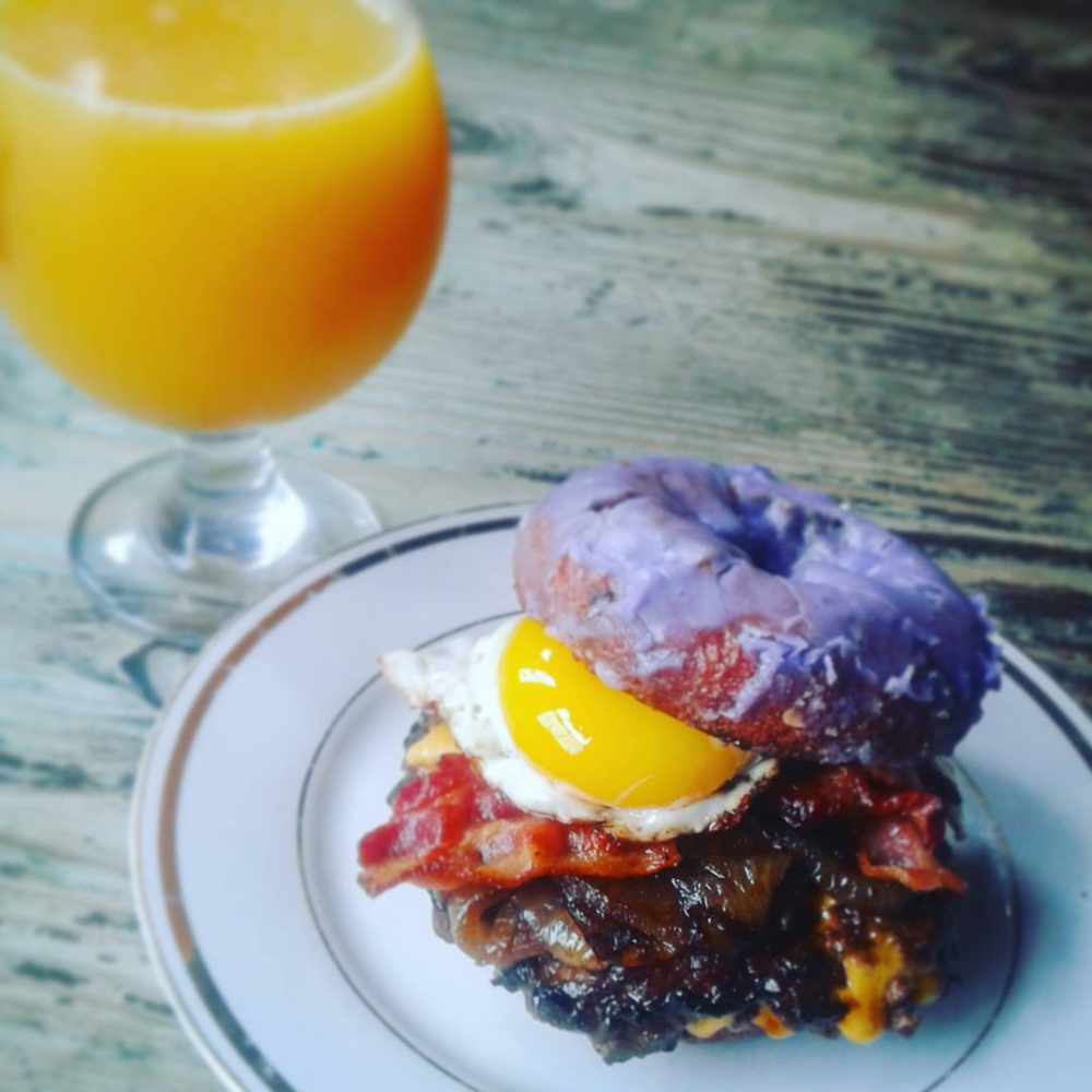 @chef_boii.r.dank with a photo of Sunday's off-menu special at Cool Beans: a cheese-stuffed burger patty with onions, bacon, and a fried egg on a blueberry cake donut from Hypnotic. Seriously.
