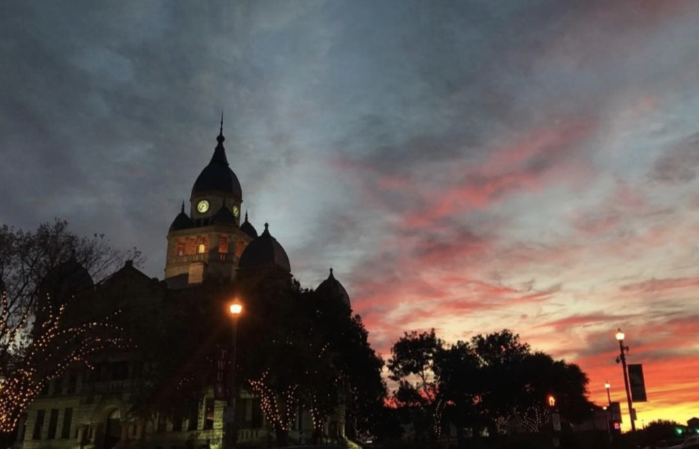 @hannahelizabethjordan with a photo of the courthouse in front of a beautiful fall sky.