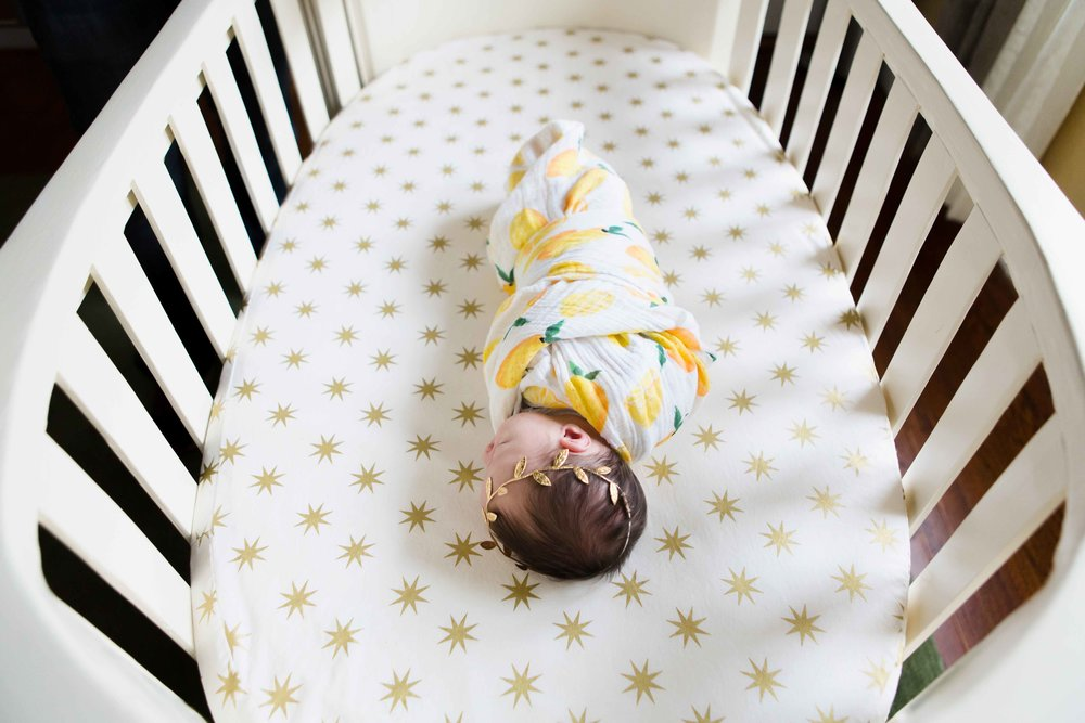 Baby girl swaddled in Little Unicorn lemon swaddle with gold headband laying in handmade white crib with gold star sheets during lifestyle newborn photo session in nursery in Oklahoma City.