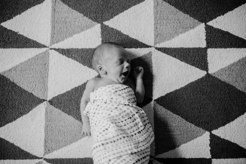 Black and White photo of newborn baby yawning while sleeping on a multicolored geometric rug, swaddled in a knitted patterned blanket comfy in Oklahoma City, Oklahoma.