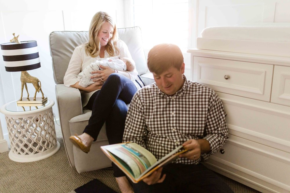 Lifestyle newborn family photos in home reading book in giraffe inspired animal themed nursery mom holding baby while dad reads children's book about Texas