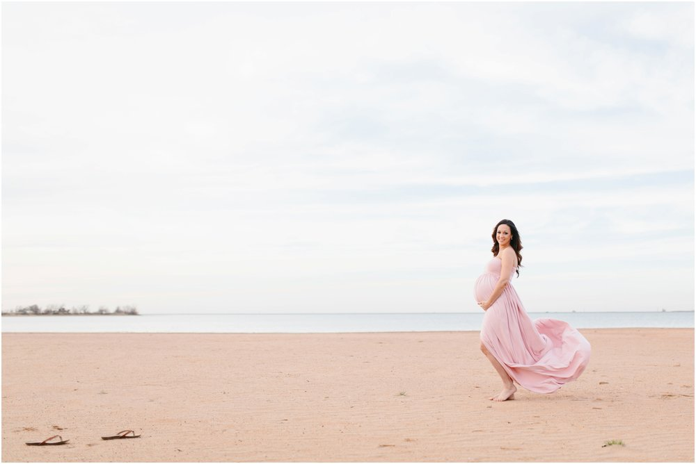 maternity flowy dress blowing in wind on beach