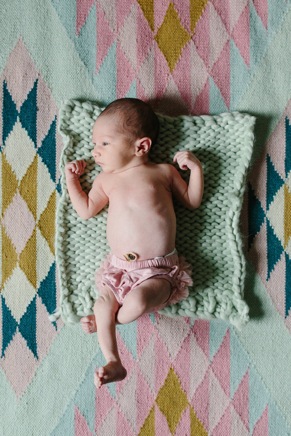 Newborn baby girl lifestyle photography session in trendy nursery, laying on mustard, mint, pink, and teal aztec rug in Edmond, Oklahoma.