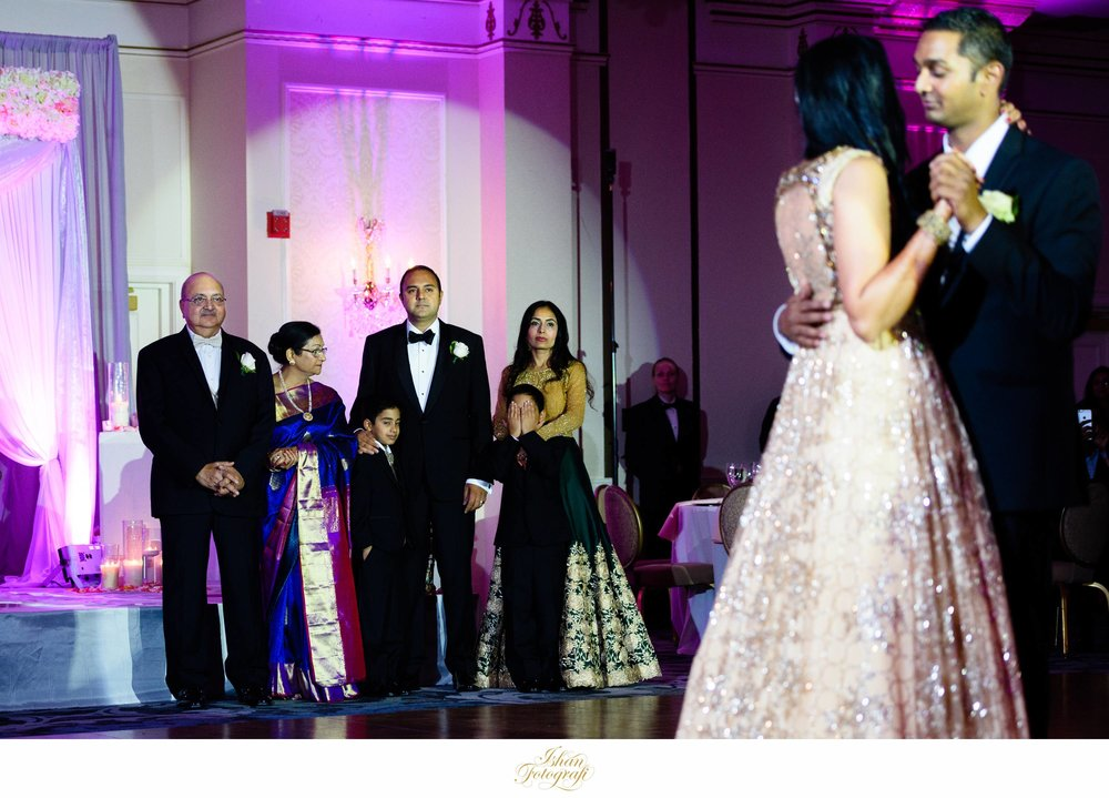 Family watching our bride and groom enjoying their first dance during their wedding reception at the hilton pearl river