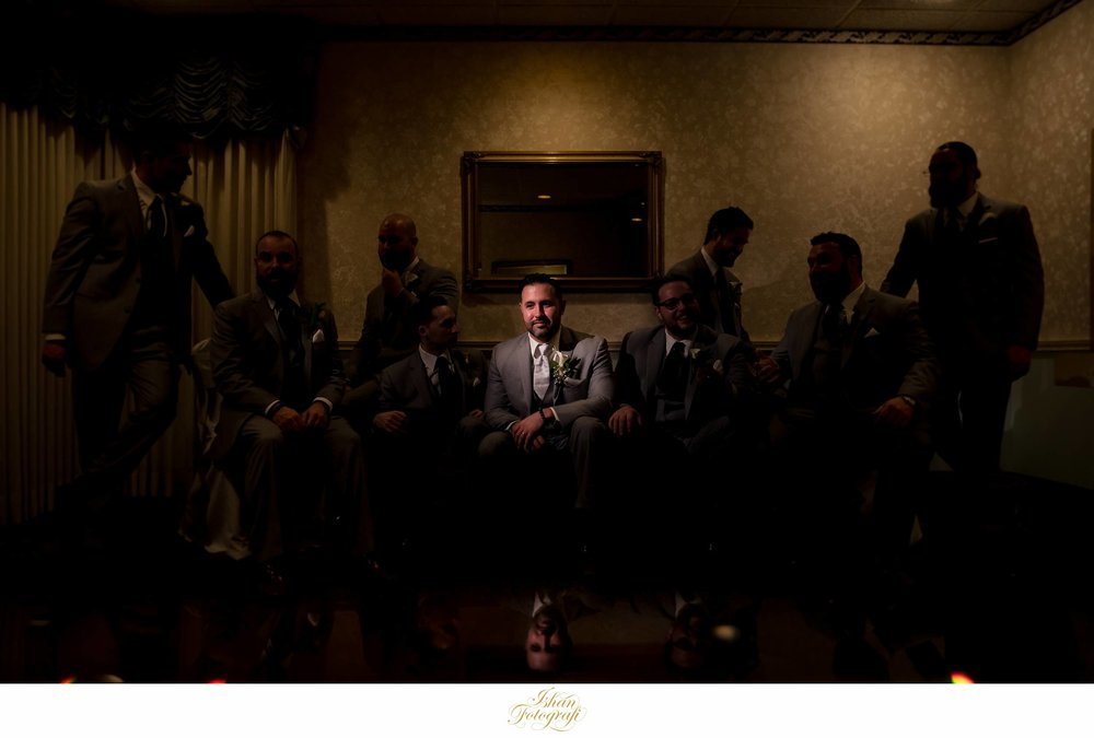 We started our day photographing the groom and his groomsmen at  The Bethwood .After photographing the casual interactions between the groom,his groomsmen and some formal photographs of the entire group, we decided to create something edgy. We wanted to isolate the groom while his groomsmen were interacting with each other so we used some dramatic lighting to achieve the look.