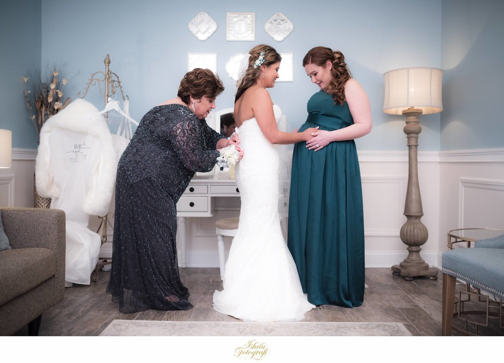 We love this moment between the bride and her maid of honor while the mom is helping our bride with her wedding gown.