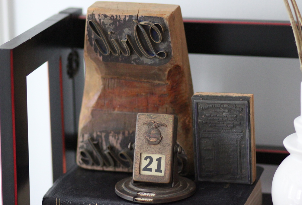 In the back is a wooden Spanish printers block that says Dril Fuerte ($155). Next to that is another printers block ($48). In the front is a rotating desk calendar ($95).