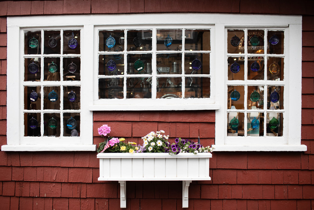 A storefront with flowers and glassware for sale.