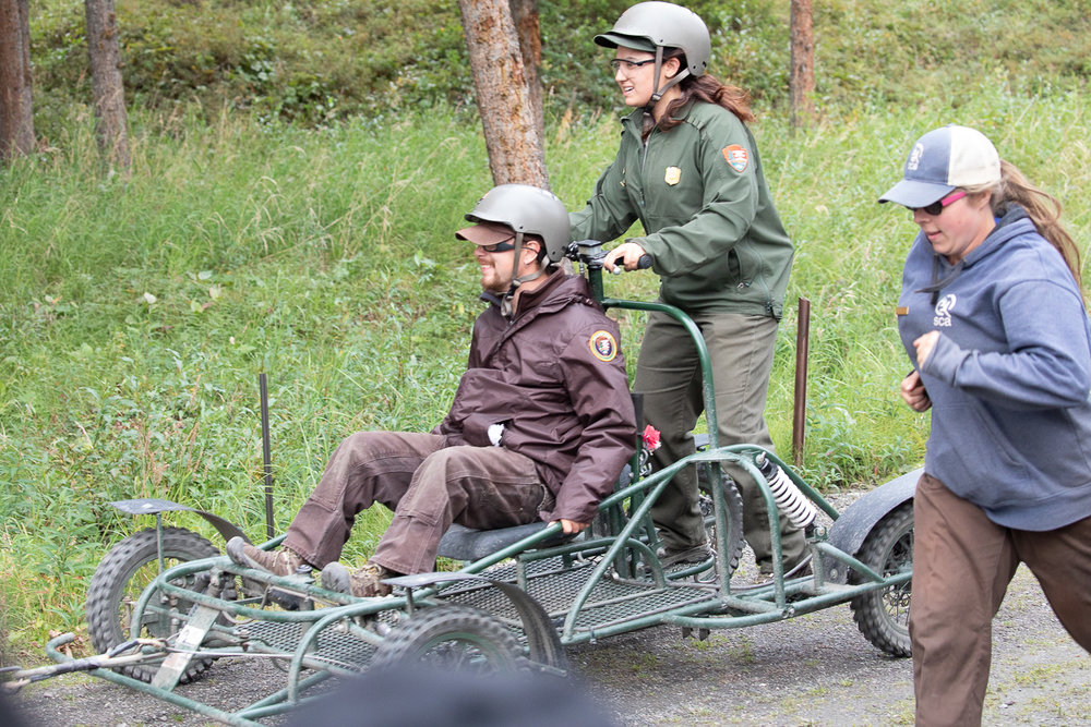The park rangers on the cart look pretty happy.