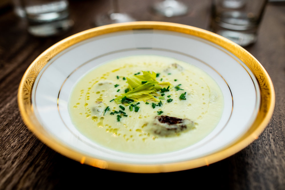Celery velouté with celery leaves, smoked morels, and lemon oil