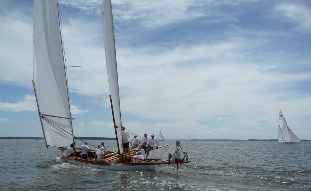 Under sail with crew on the boards.
